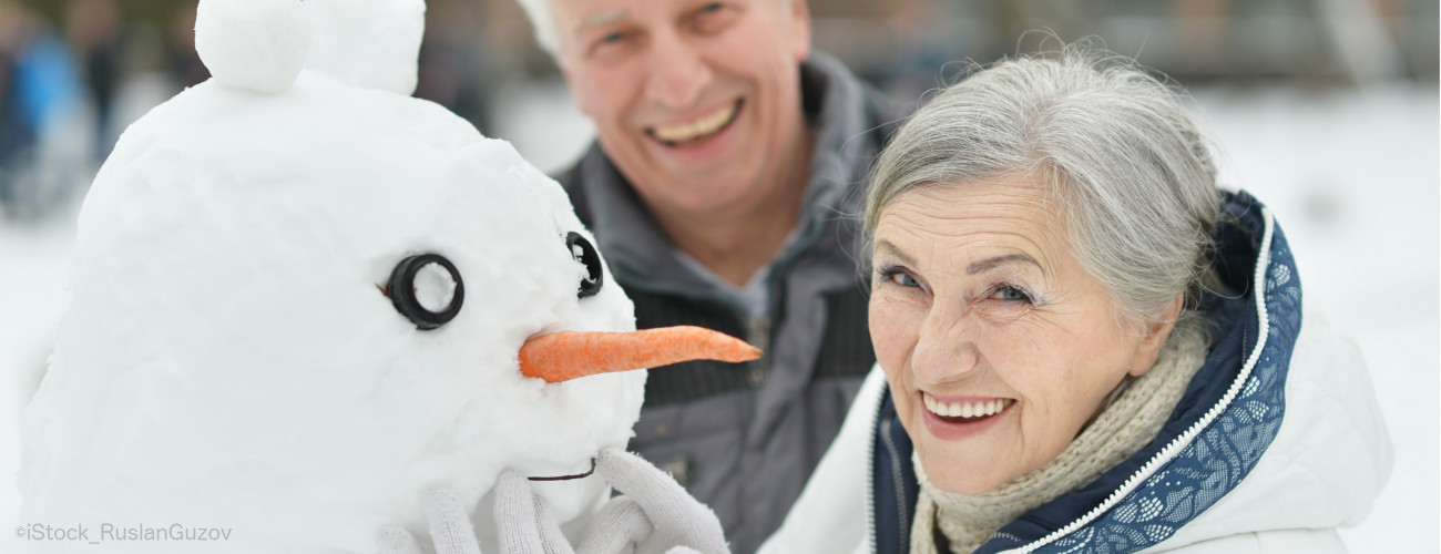 älteres paar mit Schneemann lacht