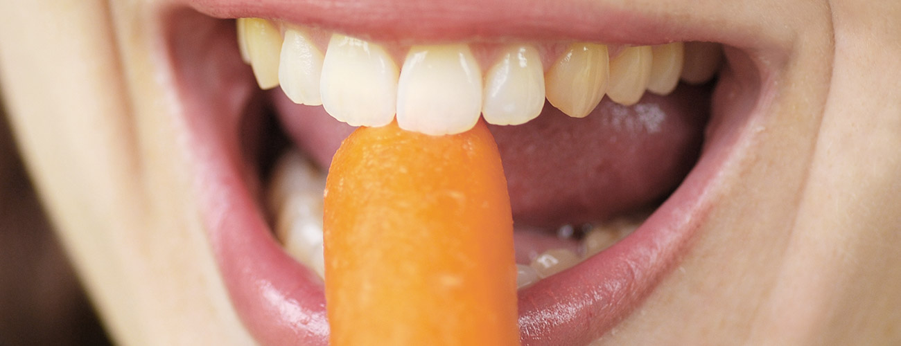 In eine knackige Möhre beißen wie die junge Frau auf dem Foto – das ermöglichen die Zahnärzte im Schloss Berlin Steglitz ihren Patienten mit Zahnersatz auf Implantaten.