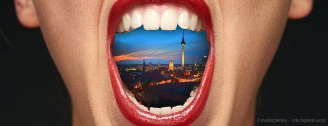Ein geöffneter Mund in Großaufnahme zeigt die Skyline von Berlin – hier verleihen die Zahnärzte im Schloss in Berlin Steglitz ihren Patienten Biss.