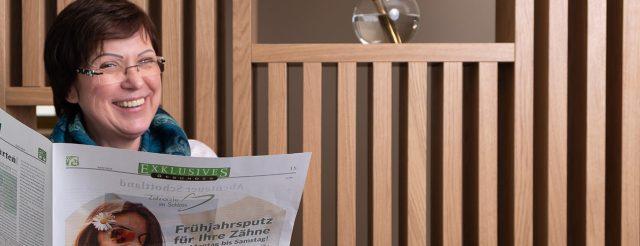 Eine zufriedene Patientin sitzt lesend in der Praxis der Zahnärzte im Schloss in Berlin Steglitz und möchte die Behandlung bewerten.