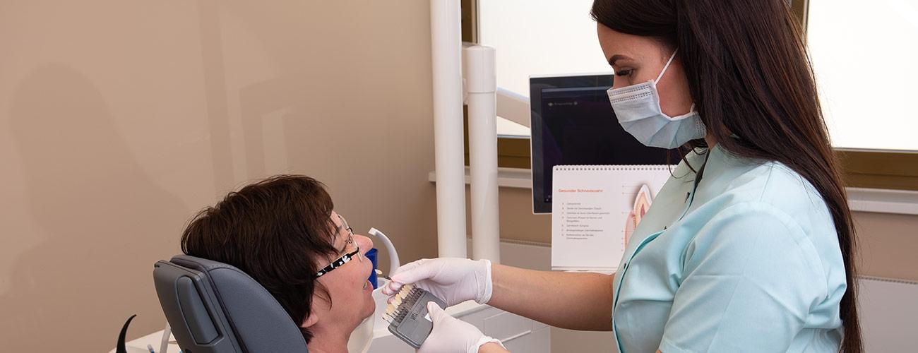 Eine Mitarbeiterin der Zahnärzte im Schloss in Berlin Steglitz bestimmt die Zahnfarbe einer Patientin für das Bleaching.