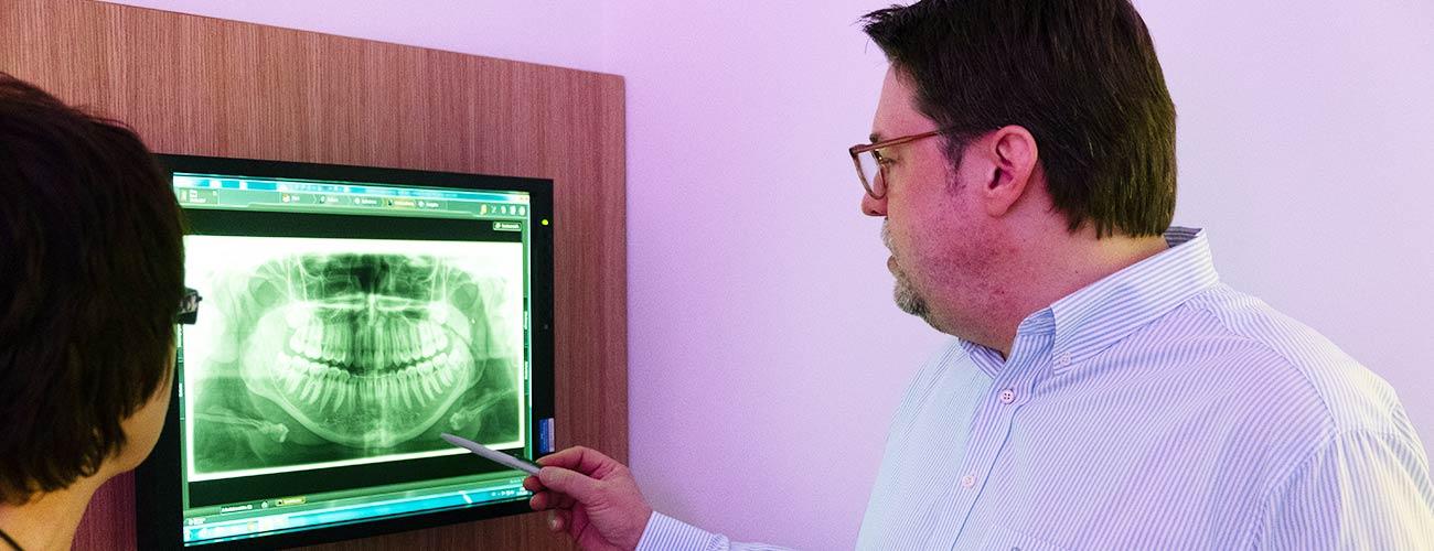 Zahnarzt Jürgen Hellmer erläutert einer Patientin eine Röntgenaufnahme aus dem Digitalen Röntgen Berlin in der Praxis der Zahnärzte im Schloss Berlin Steglitz.