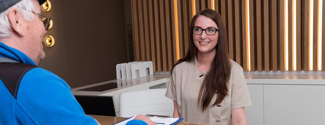 Eine Mitarbeiterin der Zahnärzte im Schloss Berlin Steglitz berät einen älteren Patienten zu den Kosten für Zahnimplantate.