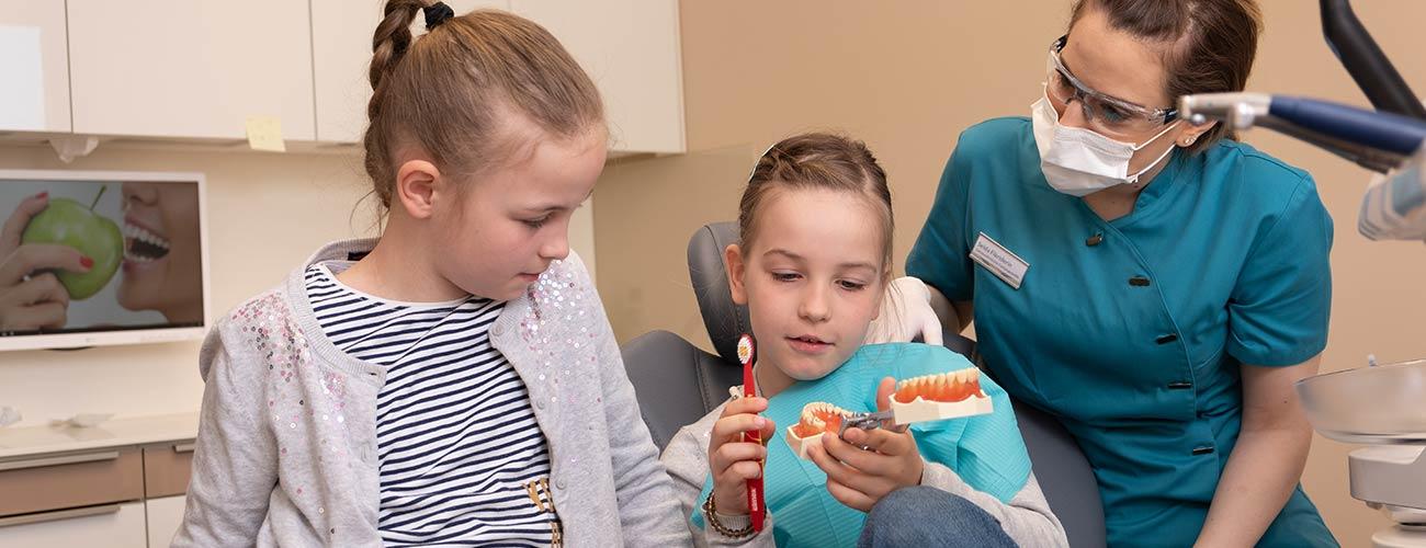 Kinderzahnarzt in Berlin Steglitz - Kinderzahnheilkunde bei Jürgen Hellmer: Eine Mitarbeiterin erklärt zwei kleinen Kindern, wie man richtig Zähne putzt.
