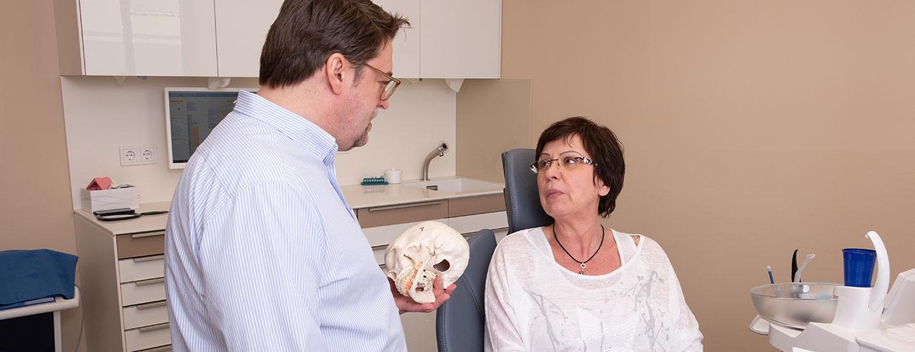 Zahnarzt Jürgen Hellmer, Zahnärzte im Schloss Berlin Steglitz, berät eine Patientin zum Thema Knochenaufbau für eine Implantation.