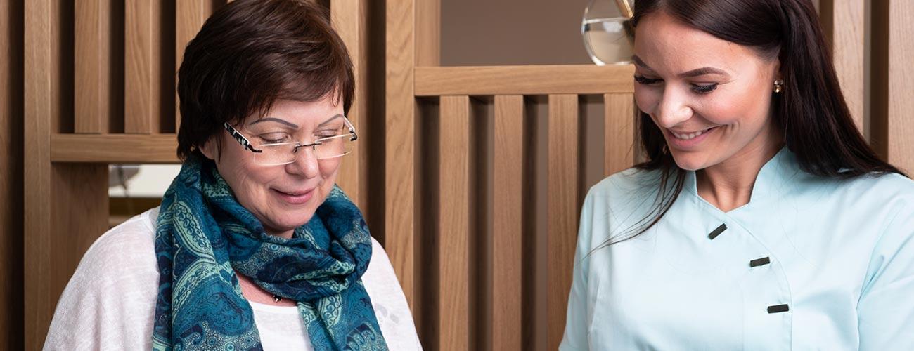 Eine Zahnärztin der Zahnärzte im Schloss in Berlin Steglitz informiert eine Patientin über die anfallenden Kosten der professionellen Zahnreinigung.