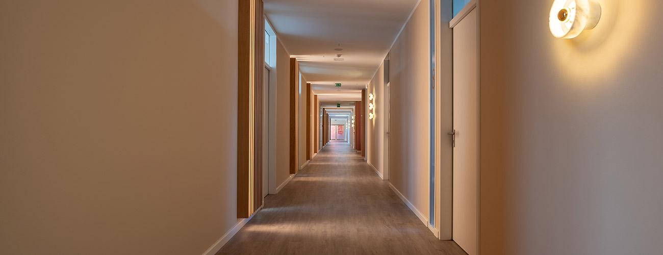 Ein langer Gang in der Praxis der Zahnärzte im Schloss Berlin Steglitz mit vielen abgehenden Türen zu beiden Seiten symbolisiert die zahlreichen privatzahnärztlichen Leistungen.