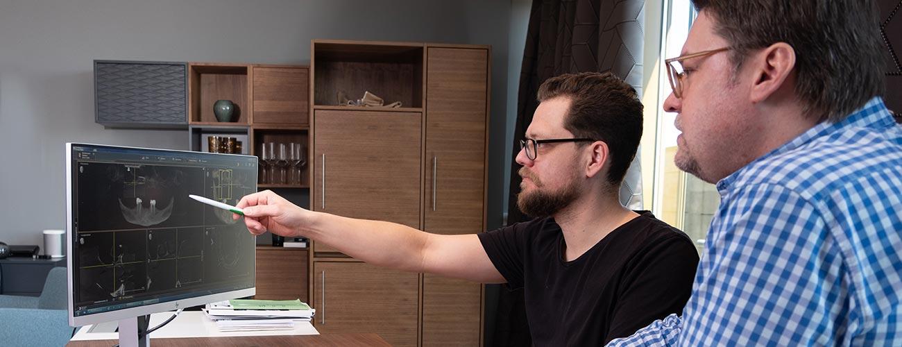 Zahnarzt Jürgen Hellmer, Zahnärzte im Schloss Berlin Steglitz, plant mit einem Kollegen eine Implantation schon vor der OP – dank der navigierten Implantologie erfolgt der Eingriff minimal-invasiv.