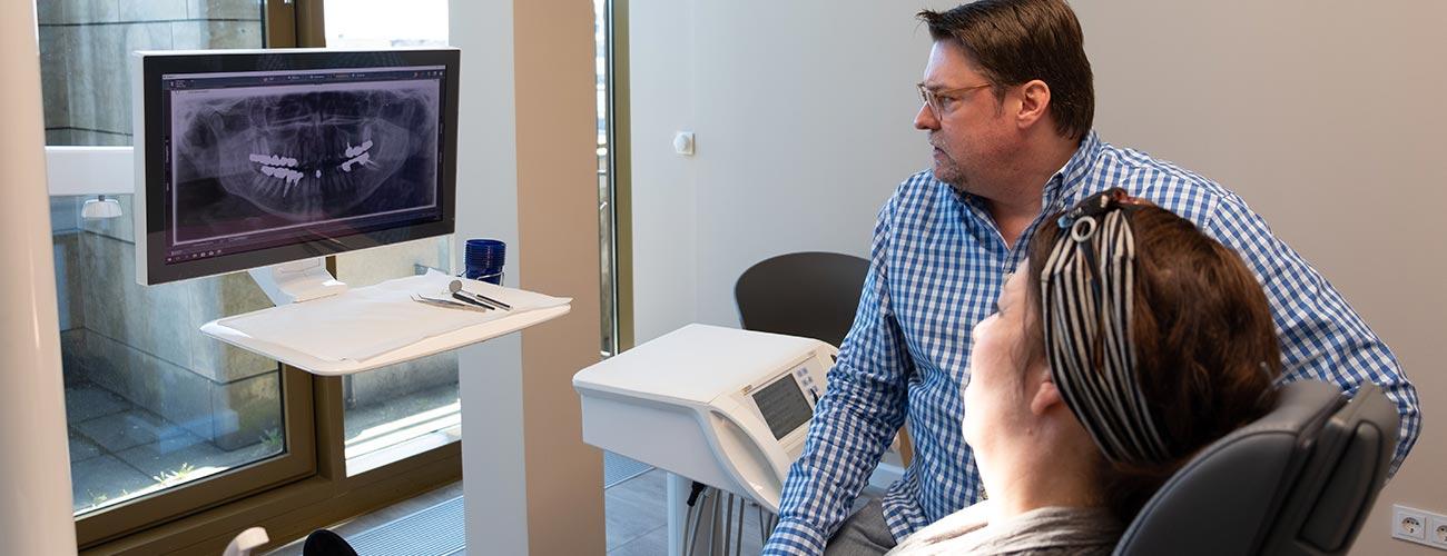 Zahnarzt Jürgen Hellmer erläutert einer Patientin mit Parodontitis das Röntgenbild und bespricht mit ihr das weitere Vorgehen bei den Zahnärzten im Schloss Berlin Steglitz.