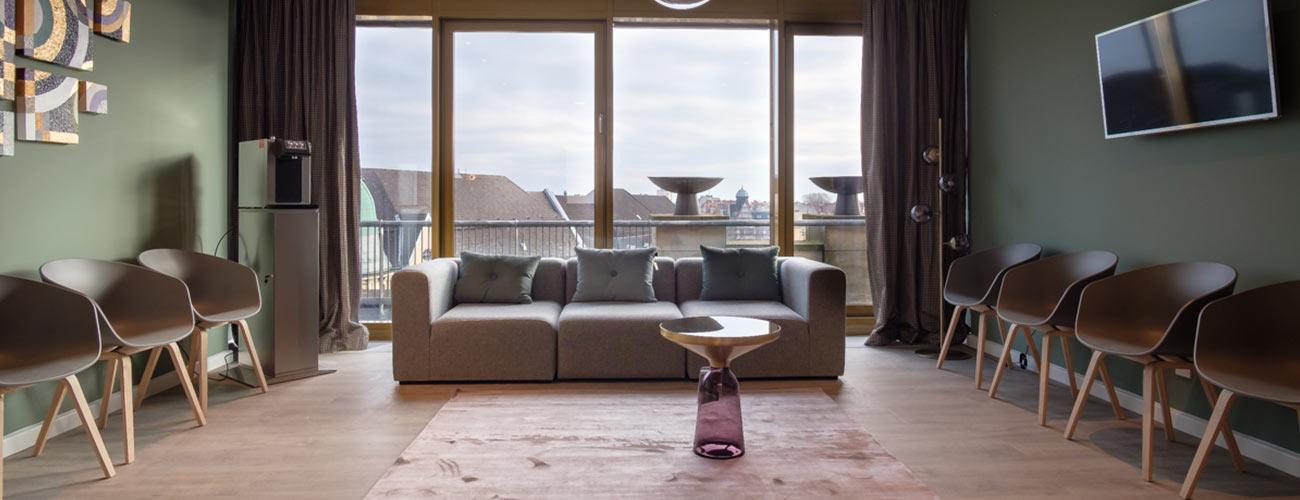 Das repräsentative Sofa vor der breiten Fensterfront in der Praxis von Zahnarzt Jürgen Hellmer bei den Zahnärzten im Schloss in Berlin Steglitz verspricht maximalen Komfort beim Warten.
