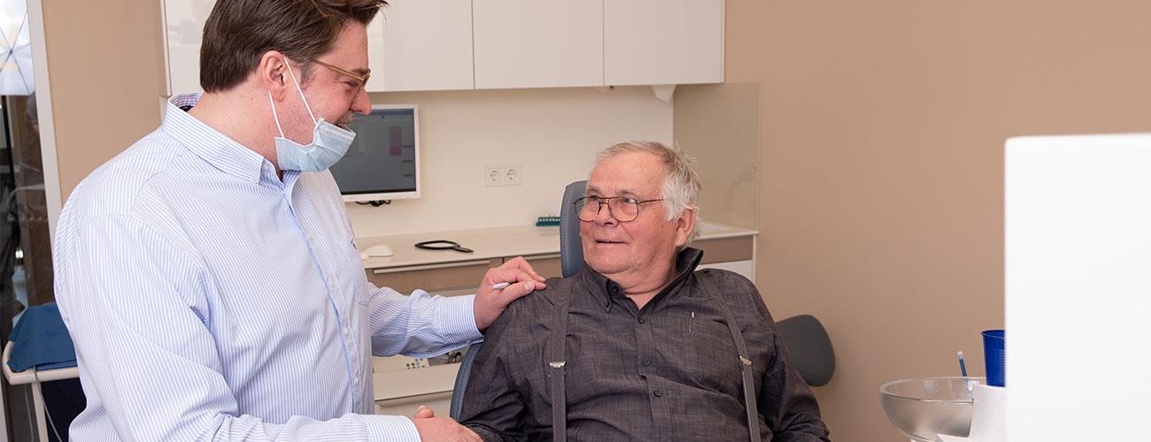 Privatzahnarzt Jürgen Hellmer berät einen älteren Patienten im Behandlungszimmer seiner Praxis Zahnärzte im Schloss Berlin Steglitz.
