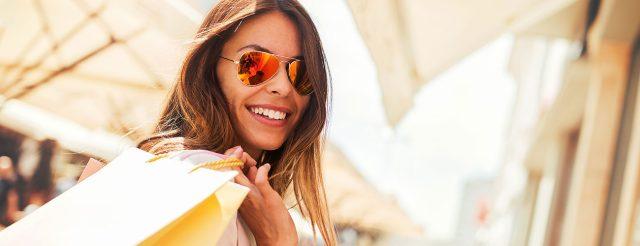 Eine junge Frau mit Sonnenbrille beim Shopping freut sich, dass die Zahnärzte im Schloss in Berlin Steglitz auch Samstag-Sprechstunde anbieten.