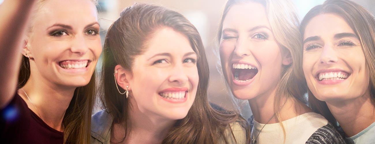 Vier attraktive lachende junge Frauen freuen sich über ein strahlendes Lächeln dank Veneers von den Zahnärzten im Schloss in Berlin Steglitz.