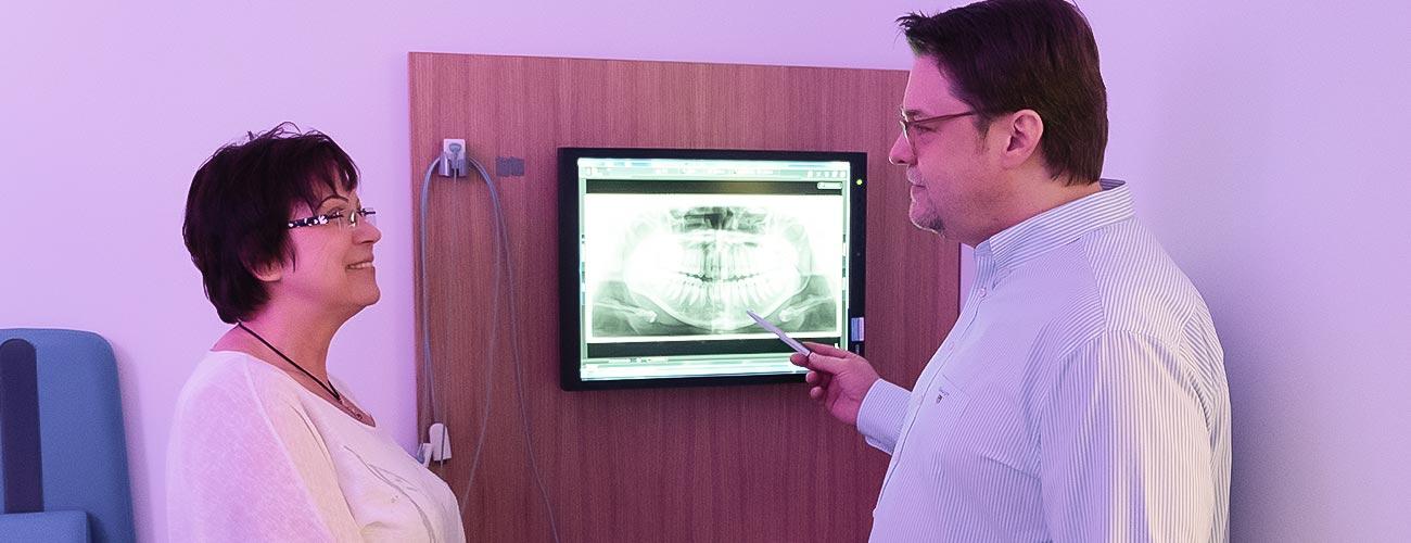 Zahnarzt Jürgen Hellmer erklärt einer Patientin, wie die Wurzelkanalbehandlung bei den Zahnärzten im Schloss in Berlin Steglitz verläuft.