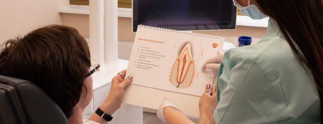 Eine Mitarbeiterin der Praxis Zahnärzte im Schloss in Berlin Steglitz erklärt einer Patientin, wie endodontische Behandlungen wie die Wurzelbehandlung oft Zähne retten.