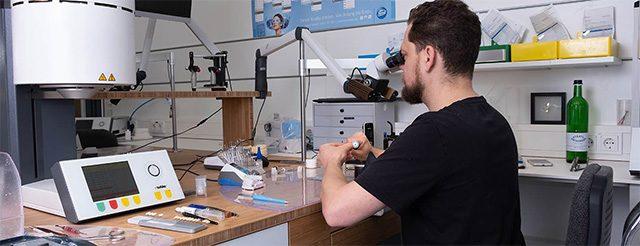 Zahntechnikermeister Chris Vörös schaut durch ein Mikroskop und fertigt ästhetischen und hochwertigen Zahnersatz im Meisterlabor dent-a-pur für die Zahnärzte im Schloss in Berlin Steglitz.