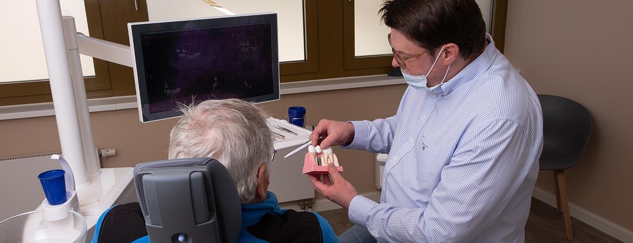 Zahnarzt Jürgen Hellmer erläutert einem Patienten anhand eines Implantat-Modells, wie er sich dessen Implantate vorstellt.